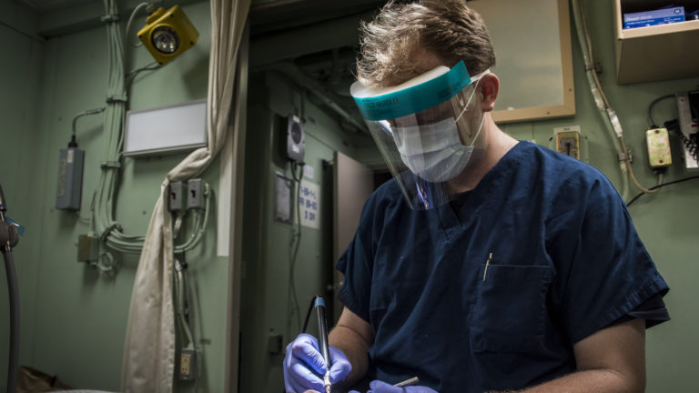 A U.S. Navy officer wears a medical face shield during a teeth cleaning. (Courtesty: U.S. Naval Forces Central Command/U.S. Fifth Fleet)
