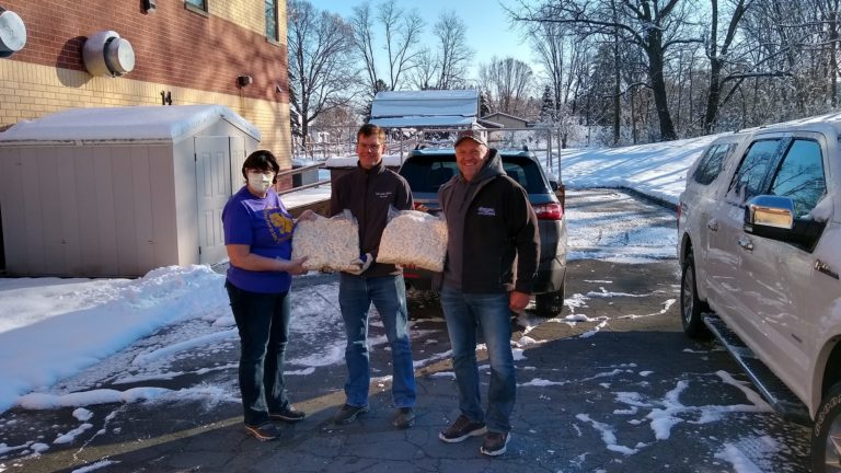 Cindy Reinhardt from the Durand Arkansaw School District accepts a donation from Steve Bechel of Eau Galle Cheese Factory and Don Weiss from Weiss Family Farms. (Courtesy: Brian Winnekins)