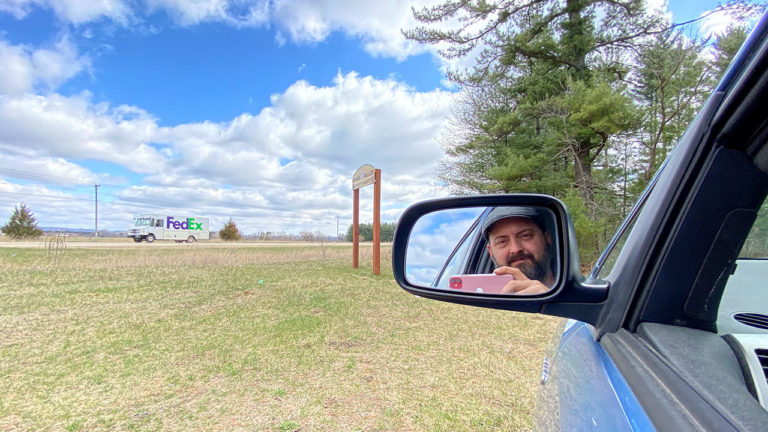 Reflection of man in car's side mirror holding cell phone