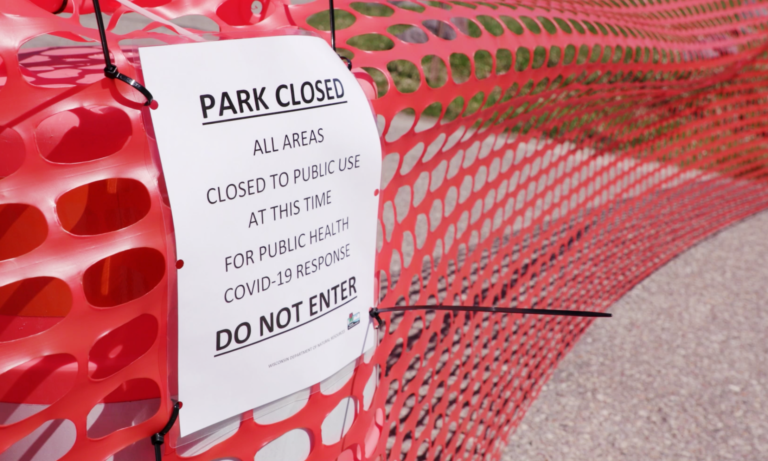 A sign notifies the public that the state park has been closed due to COVID-19.