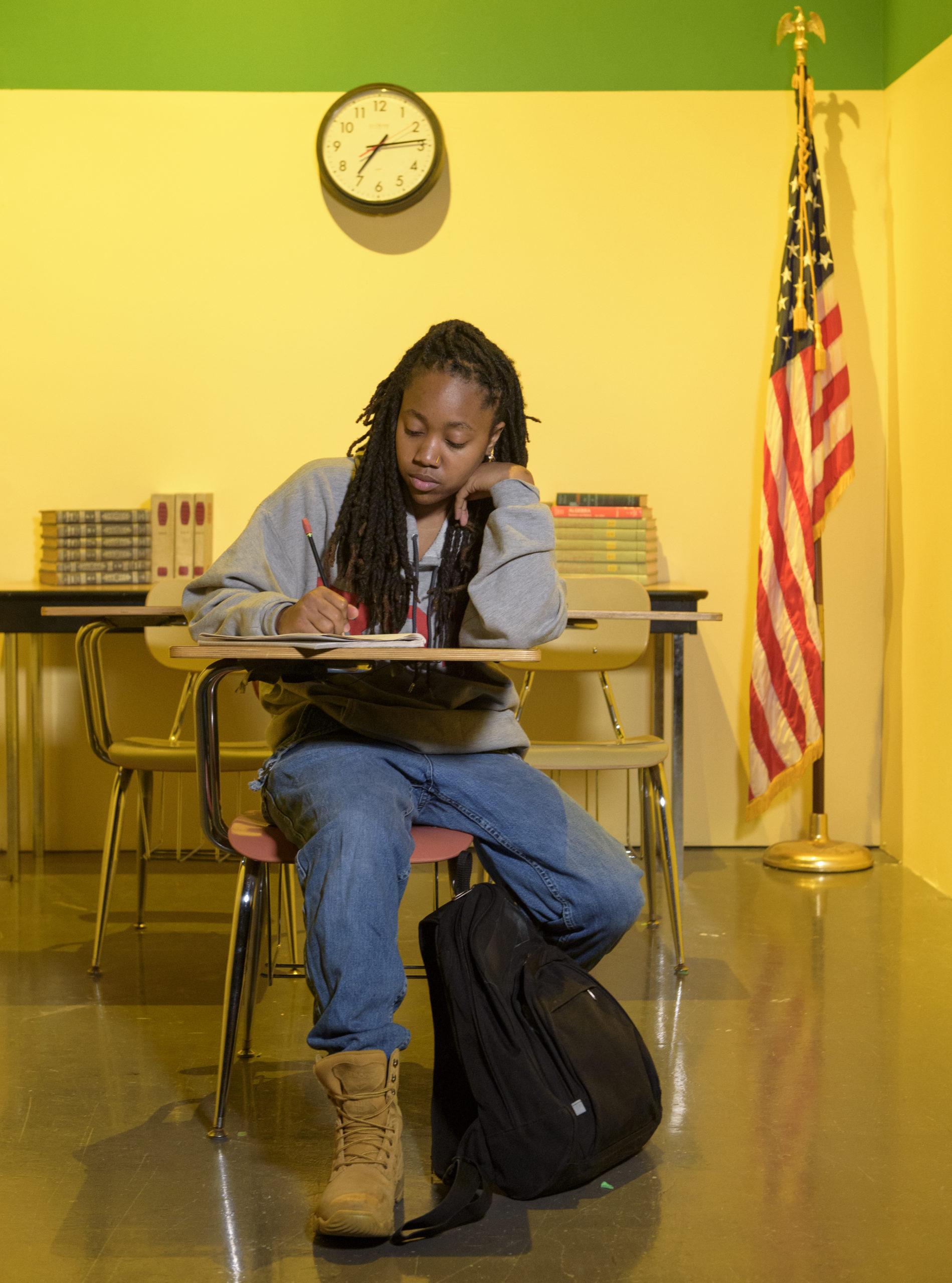 Zhalarina Sanders sits at her classroom desk.