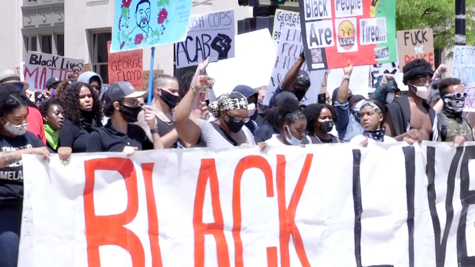 Crowed of protesters holding large Black Lives Matter sign