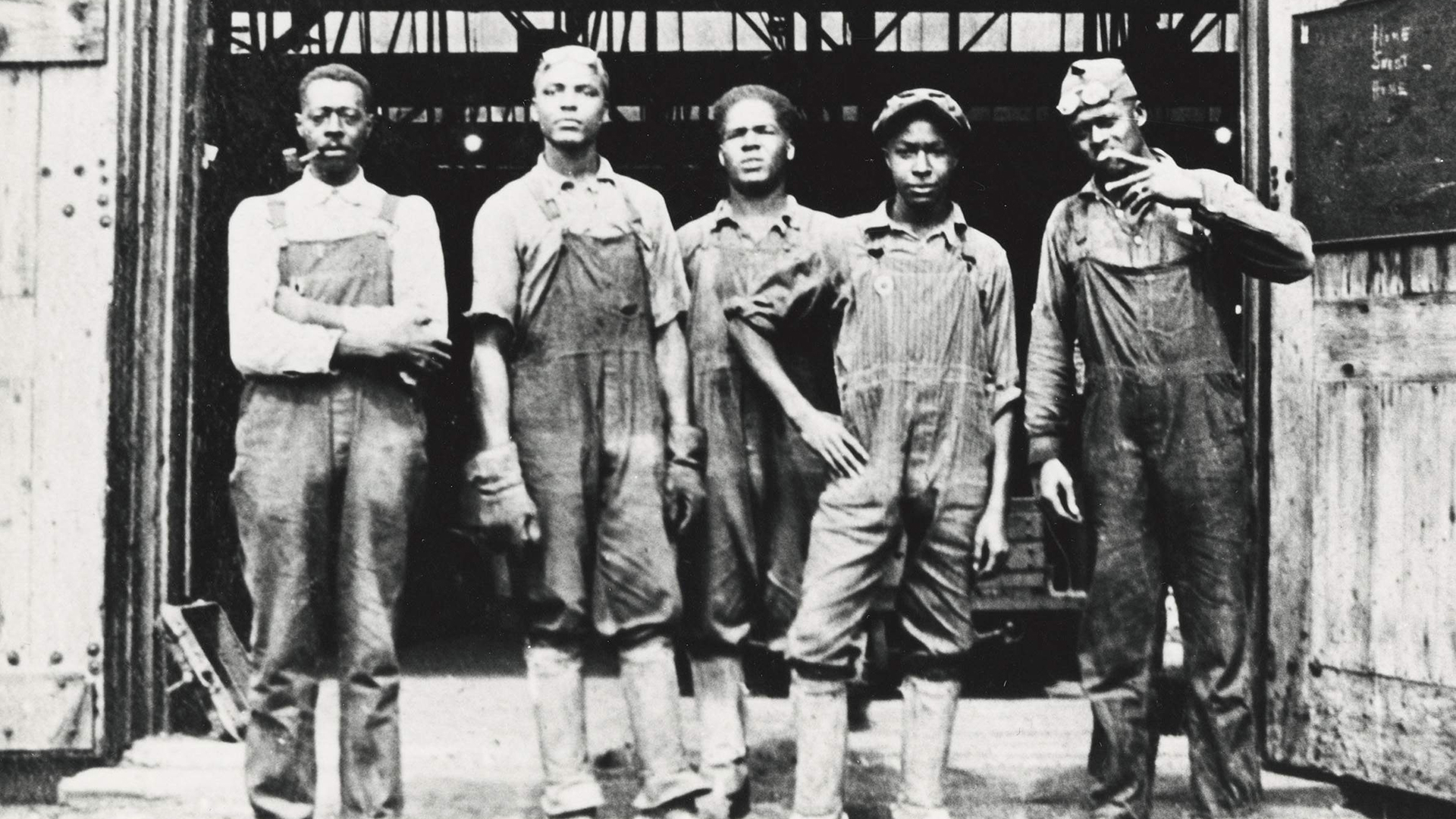 5 workmen stand in front of a warehouse.