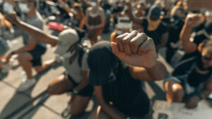 Protester in a kneeling crowd holding a fist in the air