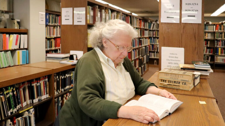 Woman reading a book in a library