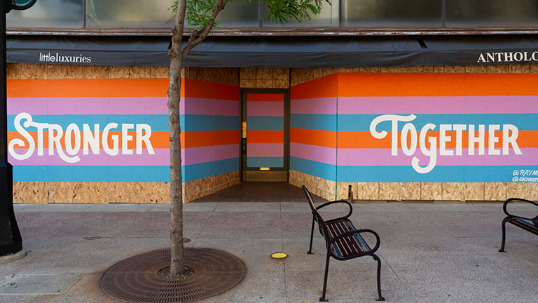 A boarded-up storefront has been repainted to say stronger together.