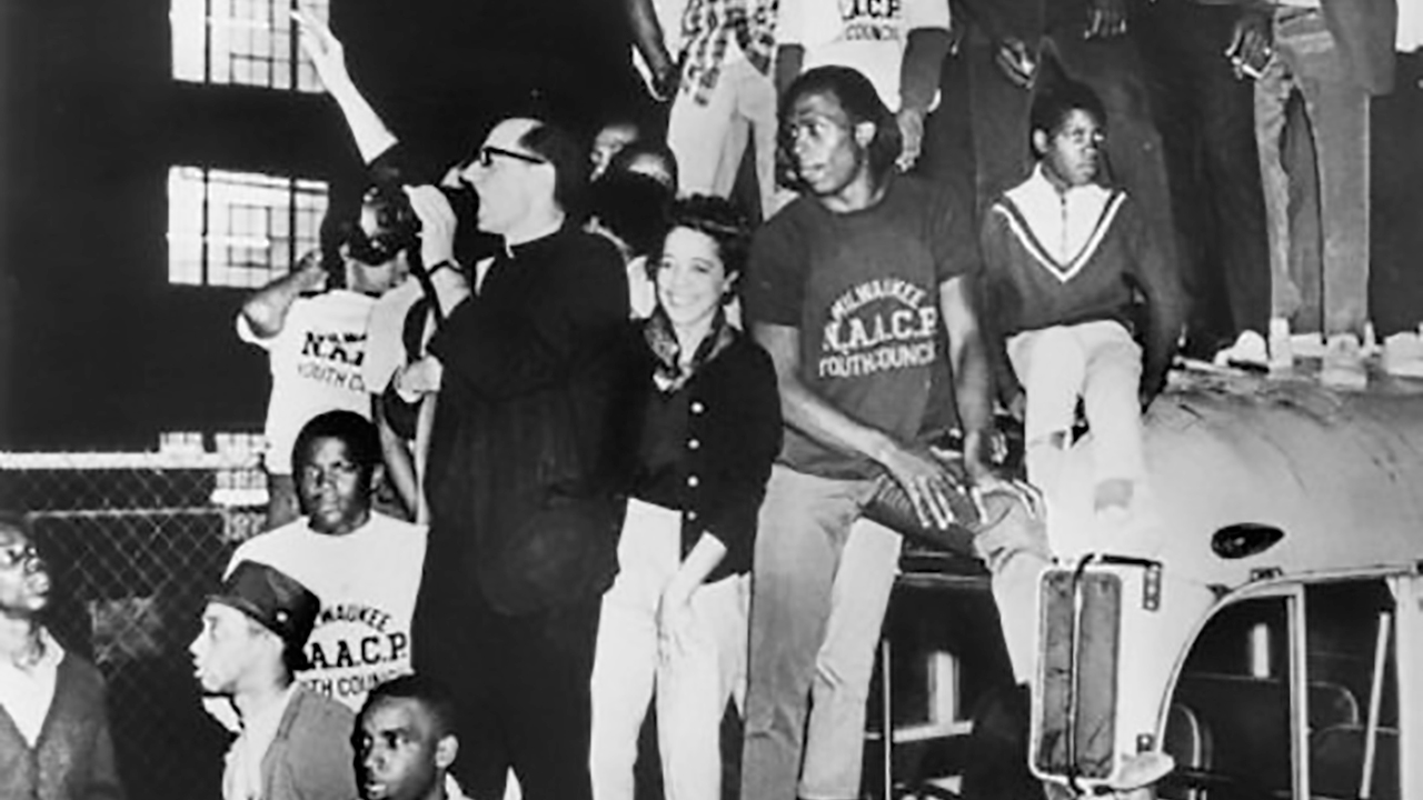 A black and white photo from the 1960s of Milwaukee antiracist activists standing on a bus