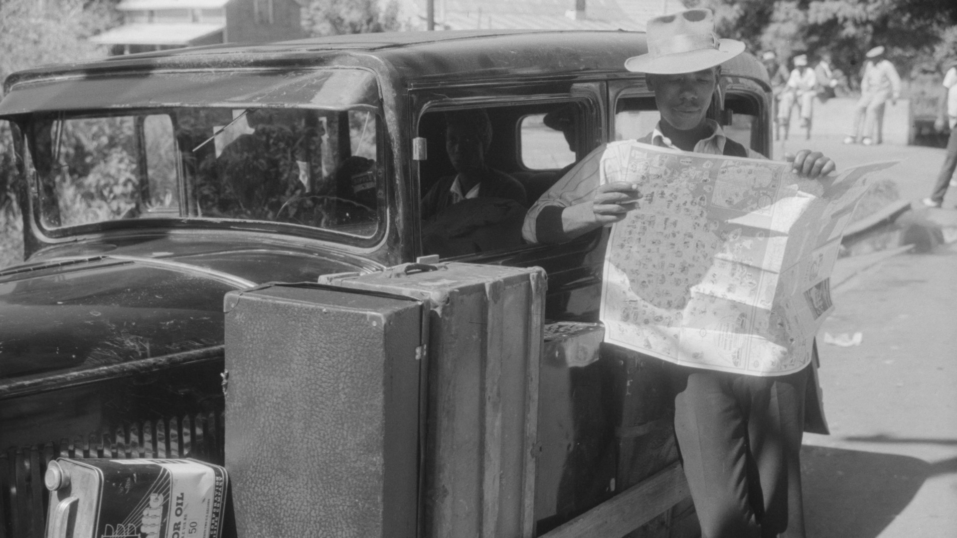 An African American man reads a road map while leaning against a car.