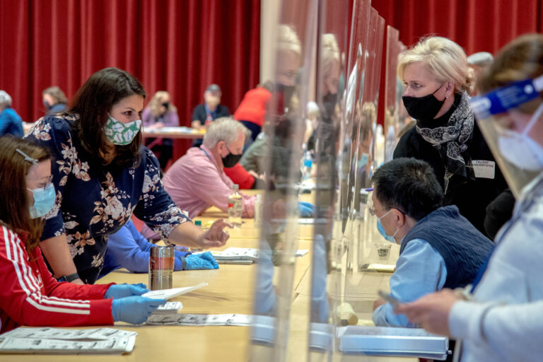 Election observers, right, look on and ask questions through plexiglass screens as officials at the Dane County recount sort through ballots by hand at the Monona Terrace in Madison, Wis., on Nov. 21, 2020. Donald Trump's campaign is paying for a recount of votes in Dane and Milwaukee counties in an effort to identify ballots to challenge the election. (Courtesy: Will Cioci / Wisconsin Watch)