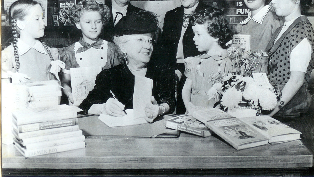 A woman author signs a book while smiling at a young girl