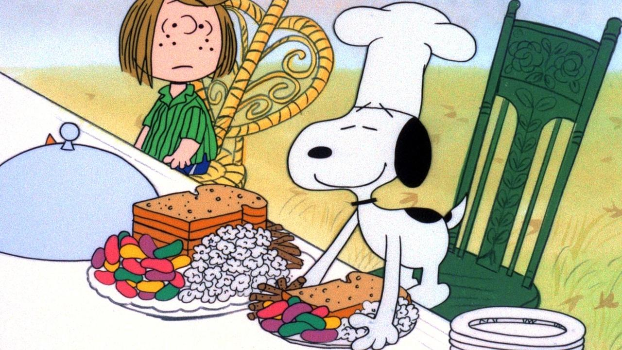 Illustration of Snoopy the dog leaning over a Thanksgiving feast