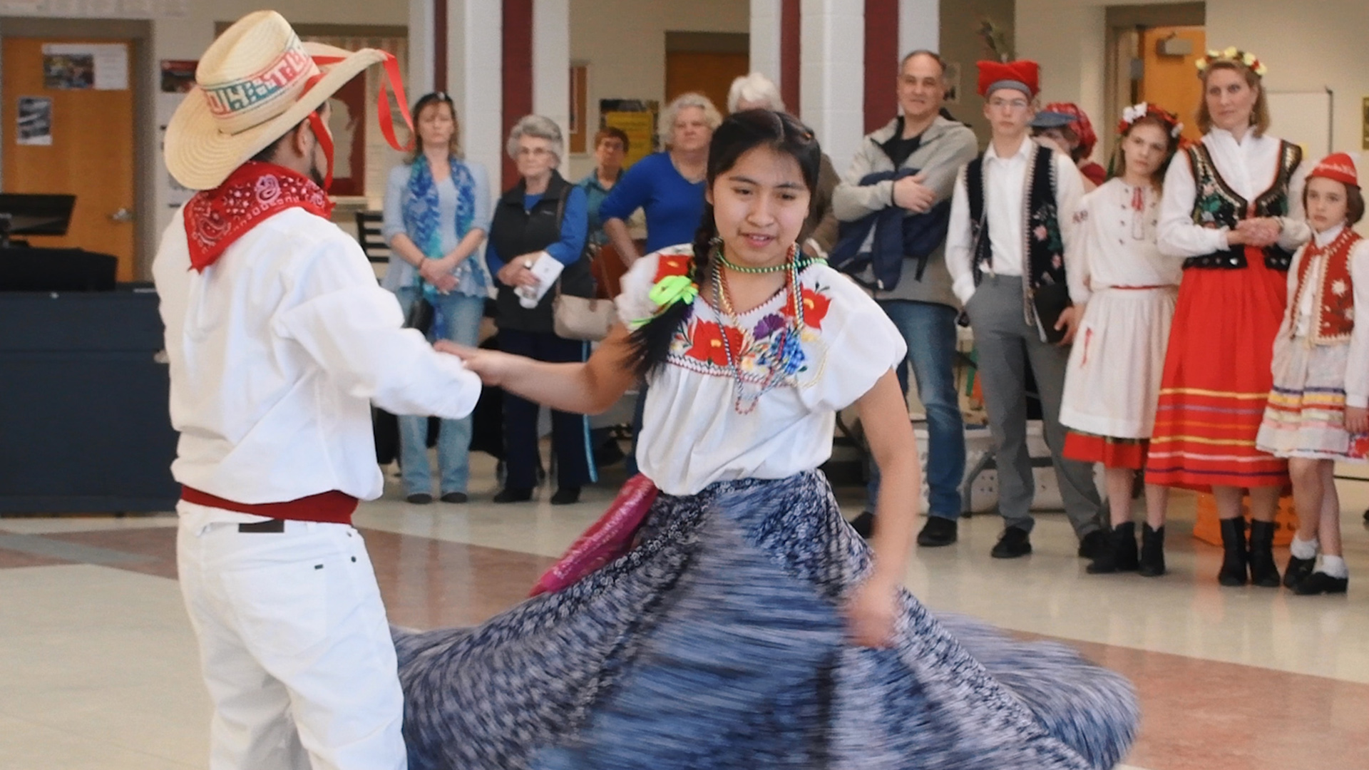 A young girl in colorful dress dances with a male partner.