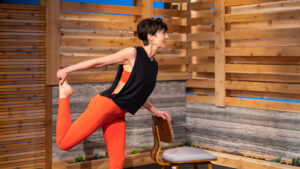 Cassy Vieth stretches her quad muscle while leaning on a chair