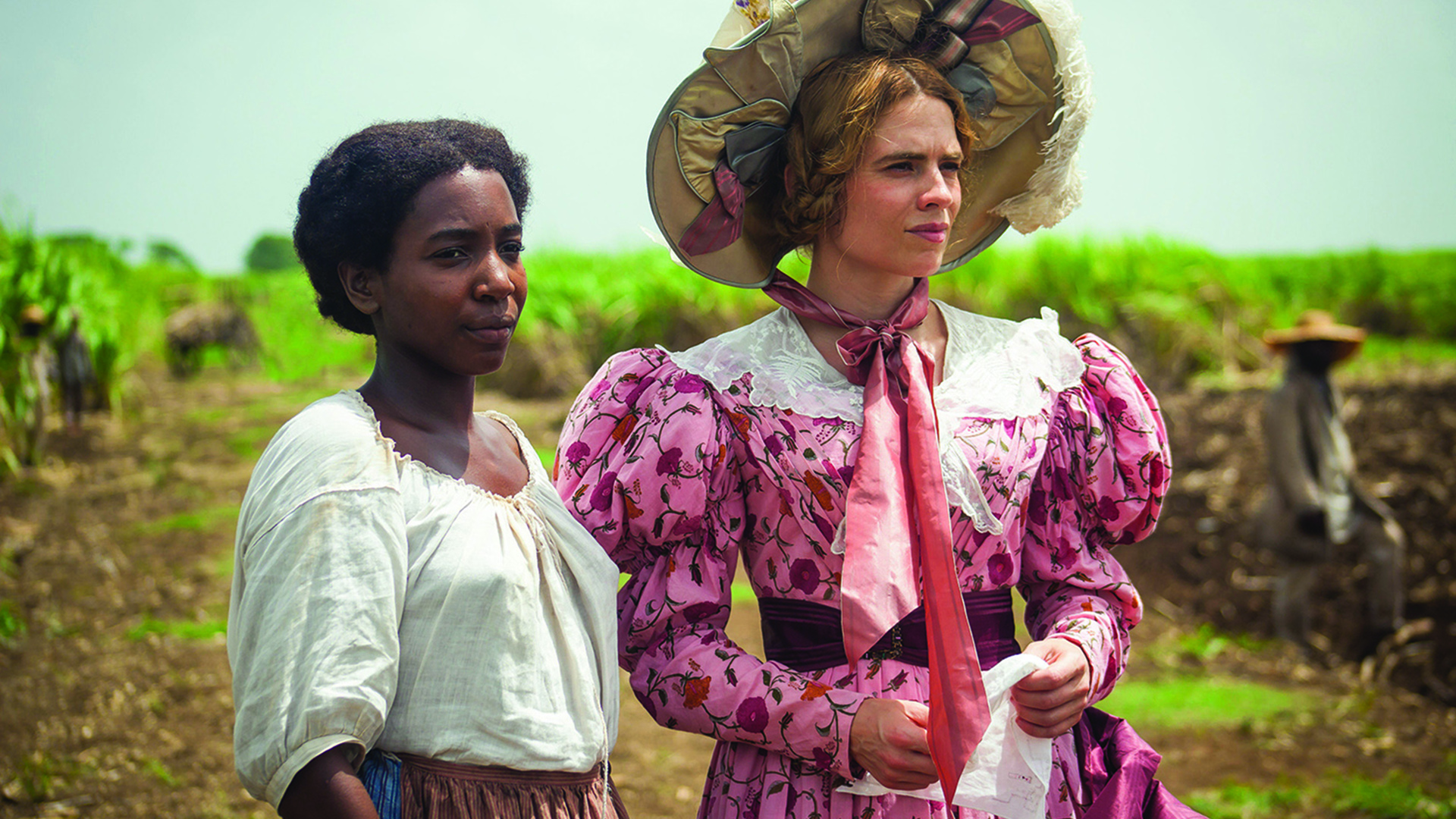 A black slave stands next to a white woman. Both look off screen into a field.