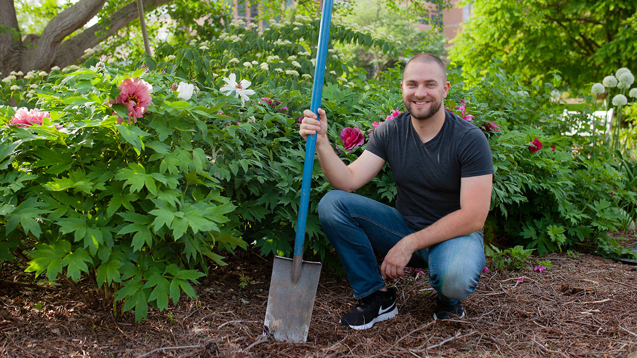 A man holds a shovel while standing in a garden.
