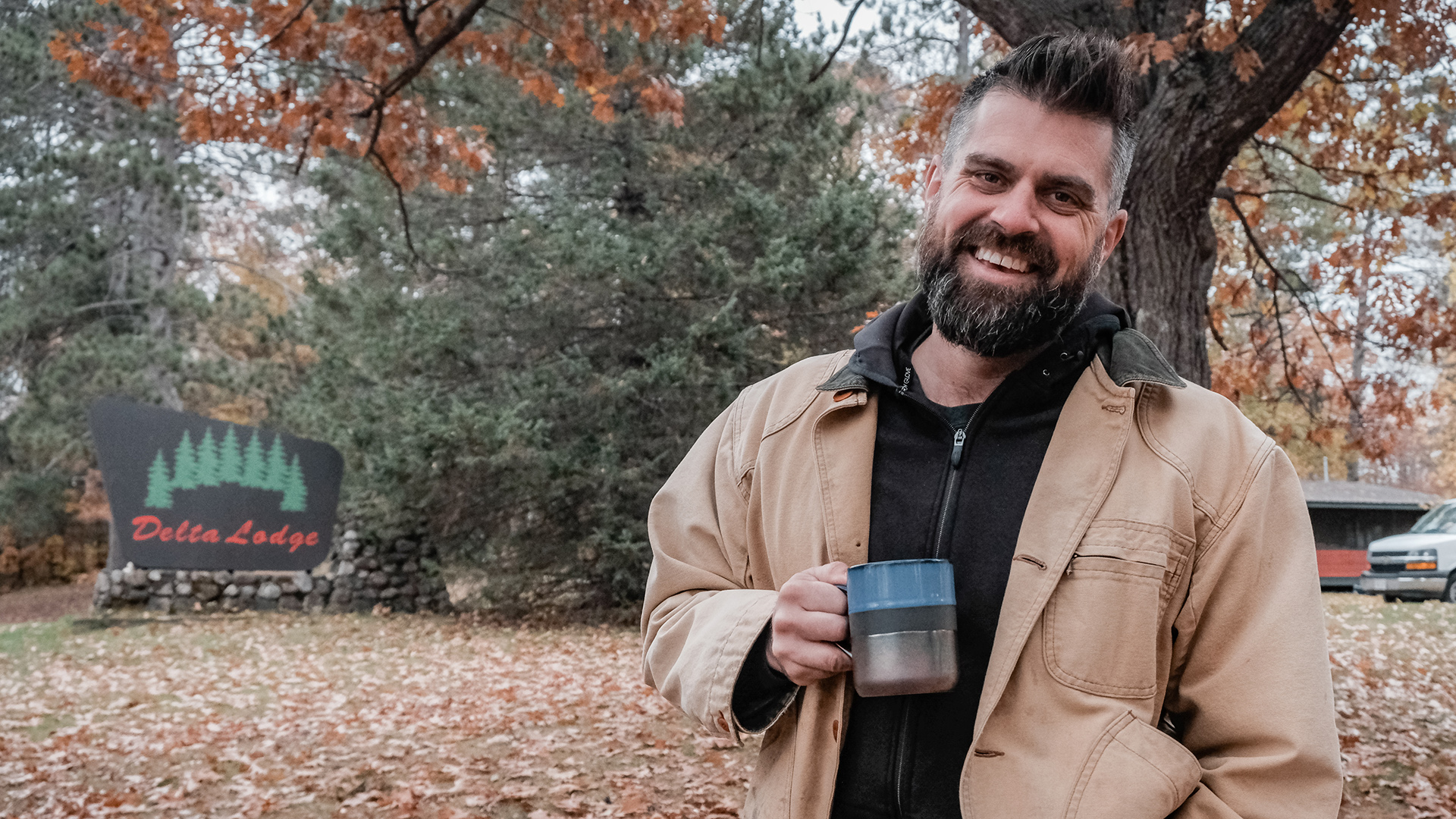 A man standing outdoors holds a coffee cup and smiles at the camera.