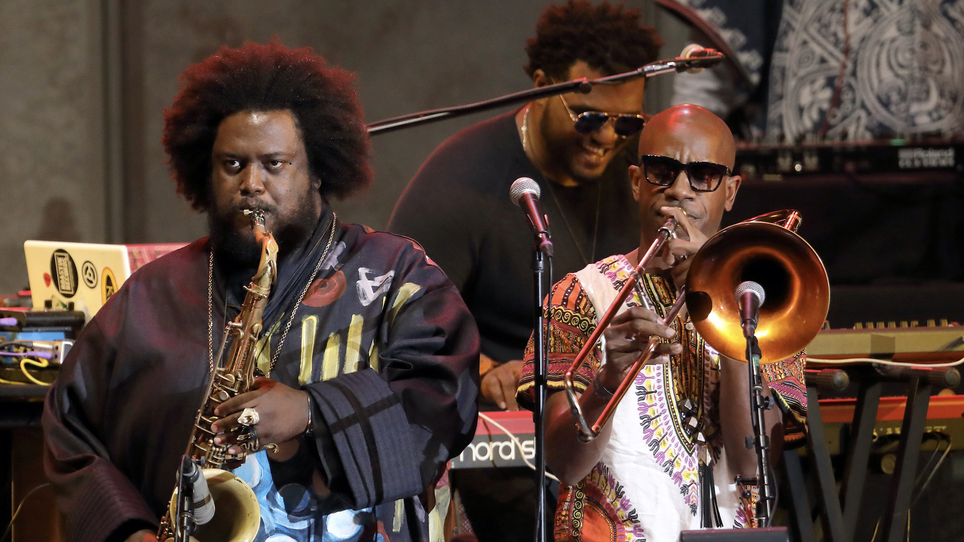 A man playing a saxophone stands on stage next to a man playing a trombone.