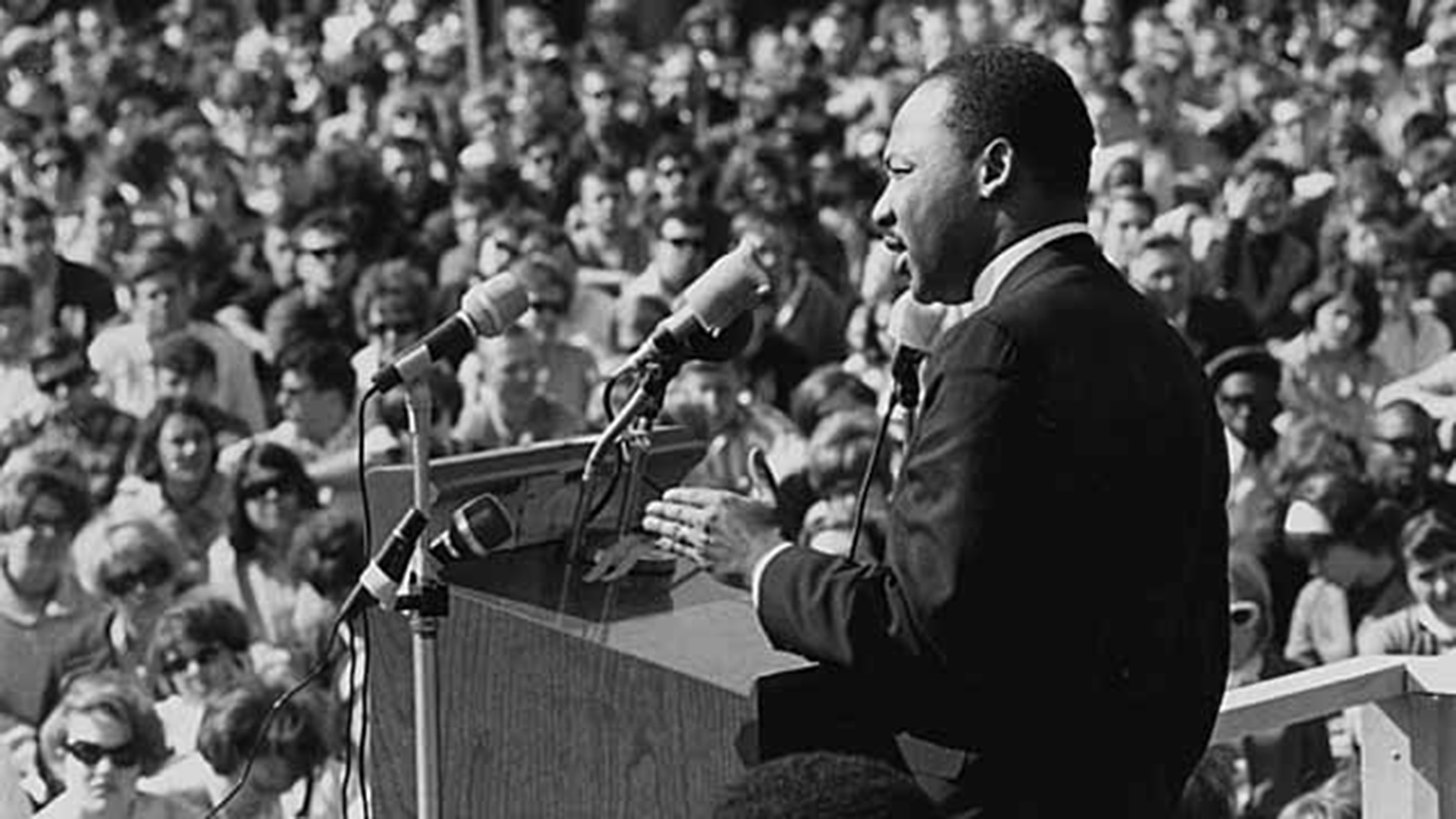 An African American man stands at a podium and addresses a crowd.