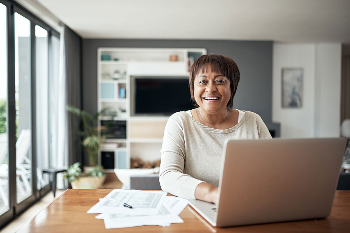 Woman on Laptop with Documents