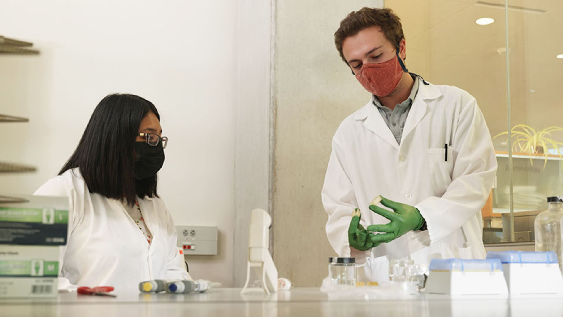 A man and woman wearing lab coats work in a science lab
