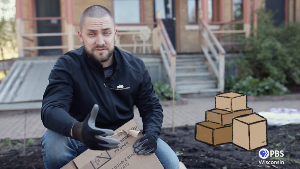 man facing camera holding cardboard box in outdoor garden