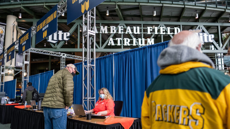 Patients stand in line to sign up for coronavirus vaccinations at a community clinic at Lambeau Field.