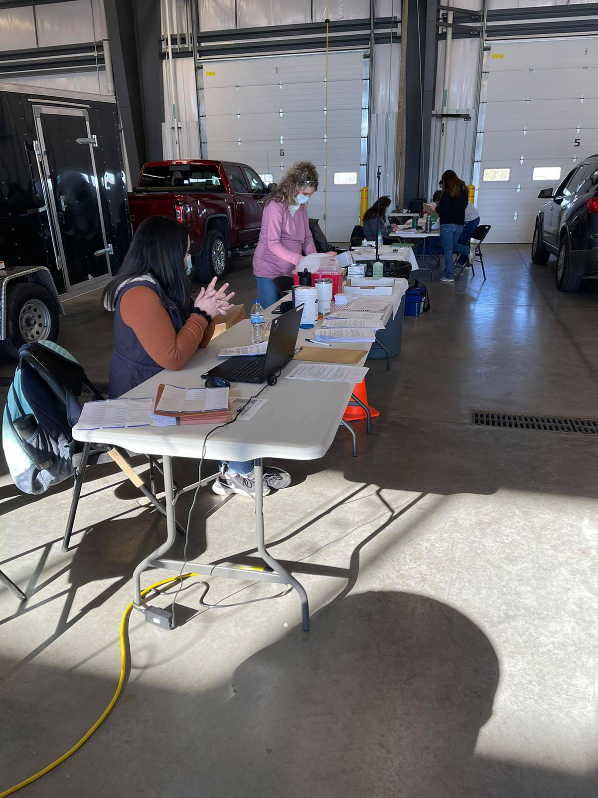 Vaccinators prepare supplies on tables inside a fire station garage