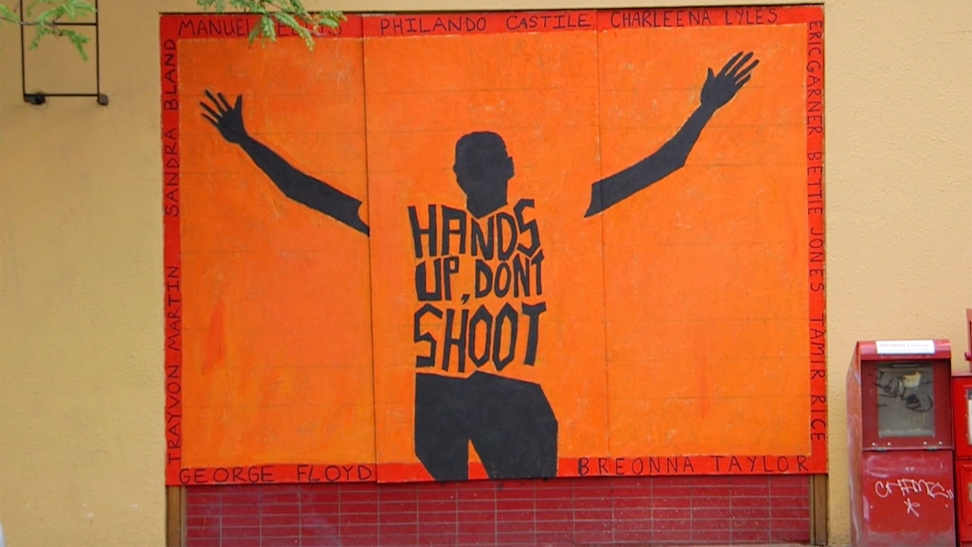 """A mural depicting the silhouette of a Black man from behind with """"Hands Up, Don't Shoot,"""" written on his back"""