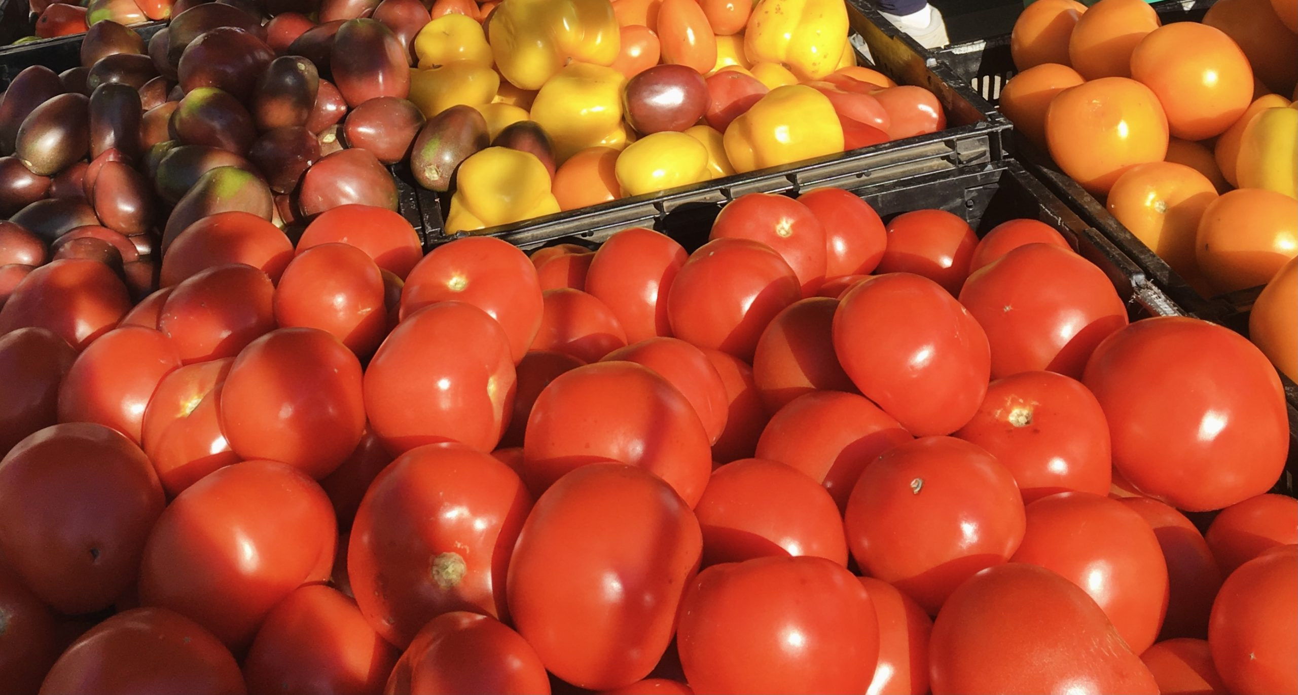 red tomatoes in a large box at a market