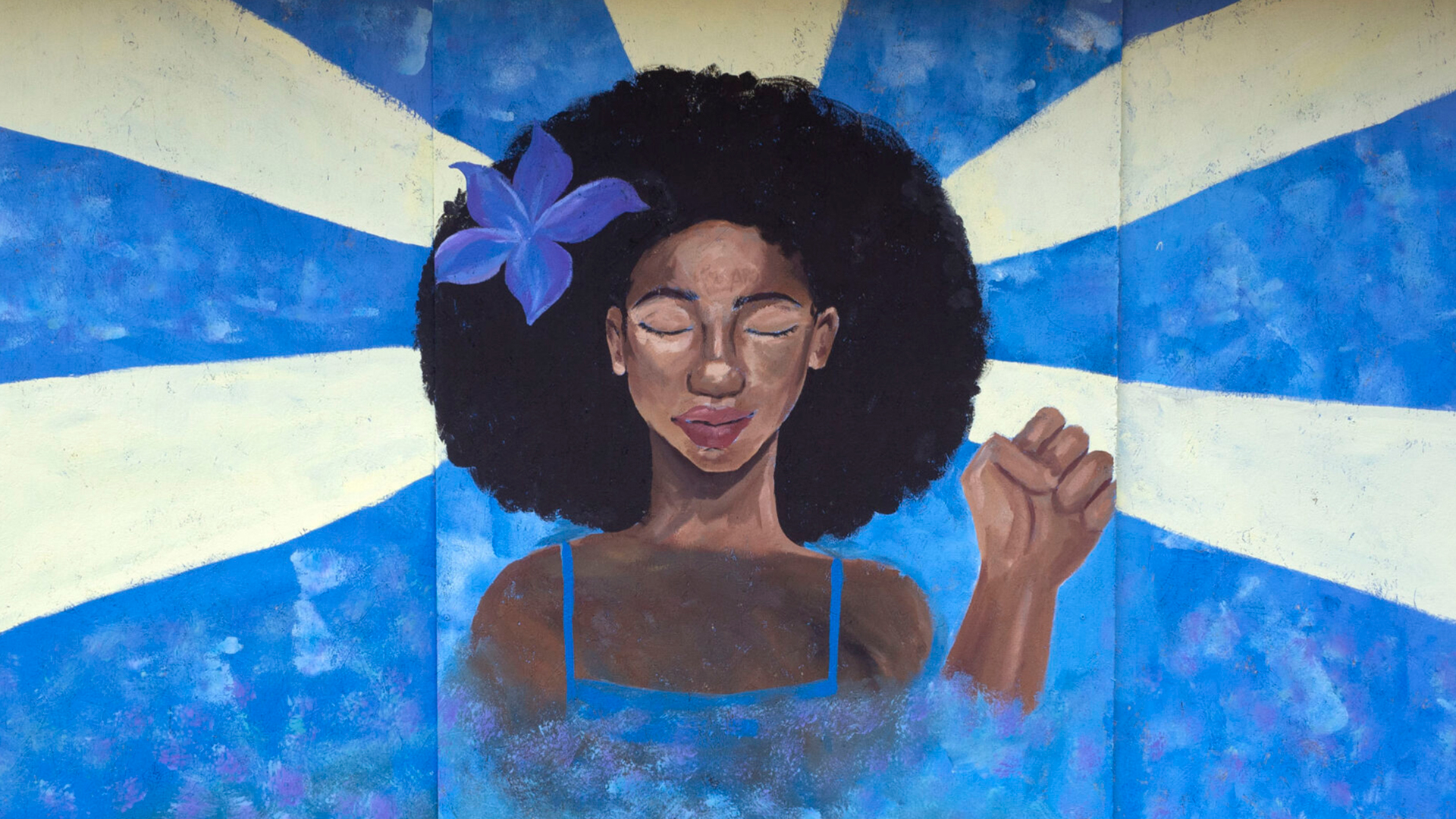 A mural depicting a Black woman with a flower in her hair, her eyes closed peacefully and holding up a Black Power fist
