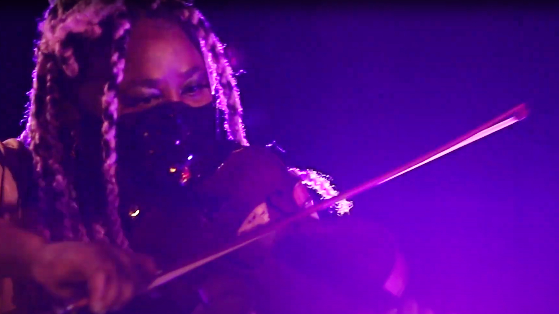 A violinist plays with a COVID mask on in low light