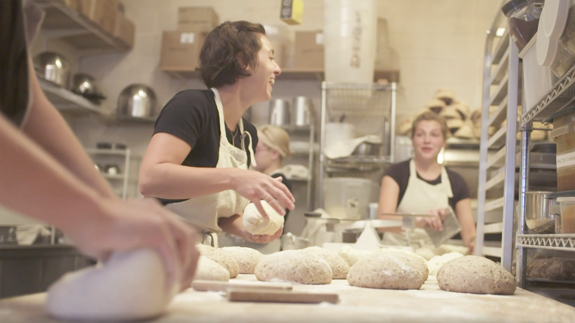 Women stand in a commercial baking kitchen handling loaves of dough