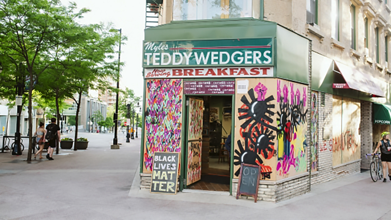 A restaurant storefront with protest art covering the front