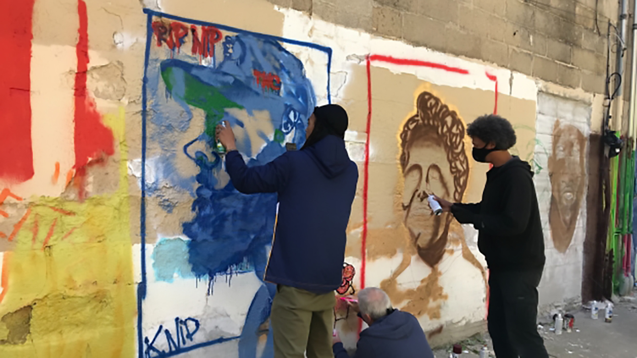 Two men paint protest art on a wall