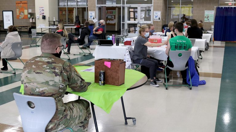 A Wisconsin National Guard member sits at a table at as vaccinators give coronavirus vaccines to patients at other tables.