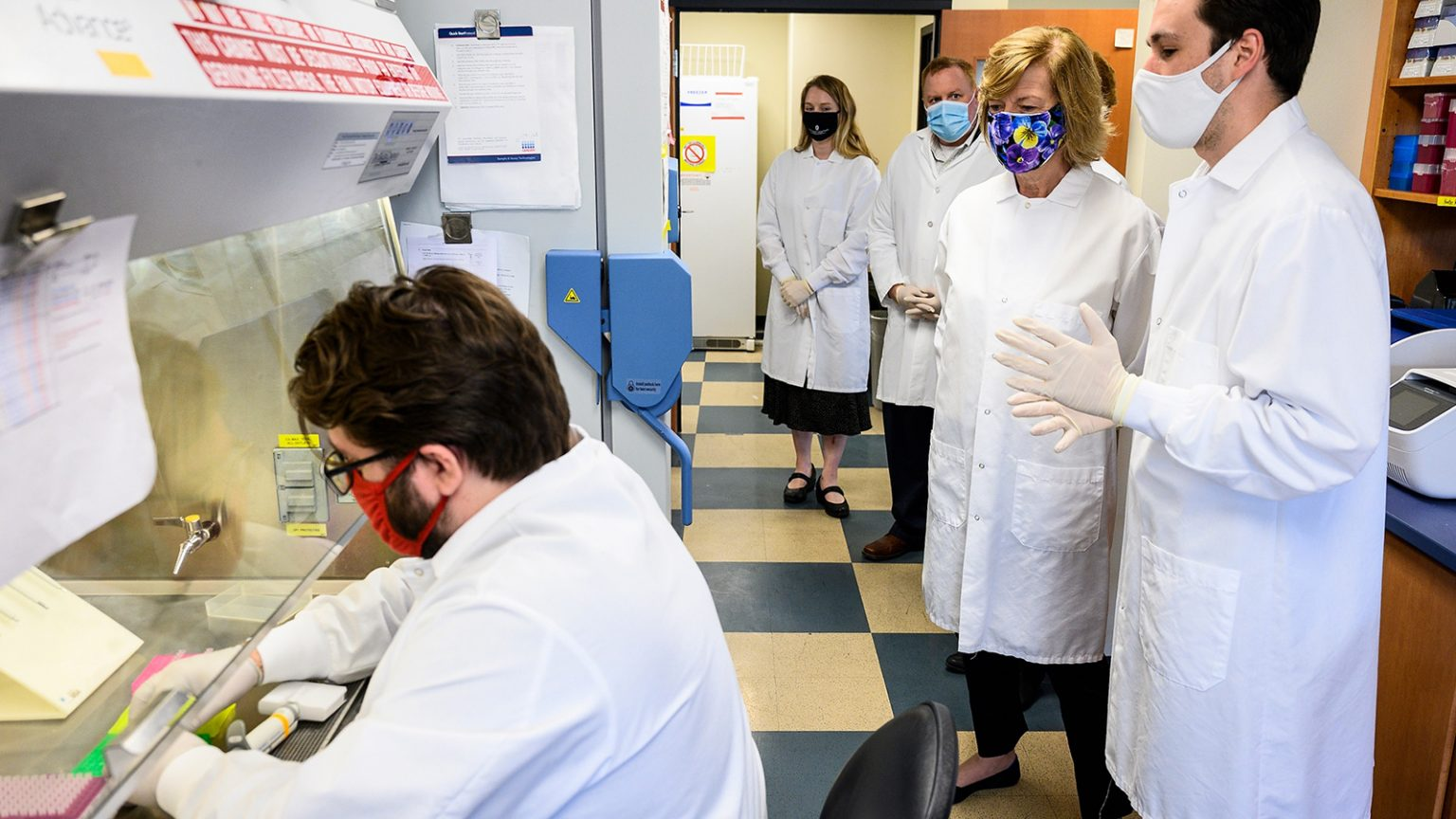 Sen. Tammy Baldwin and scientists watch research in a laboratory.