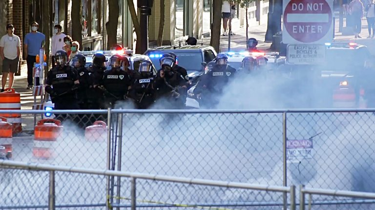 Temporary fencing and tear gas in front of a line of police officers
