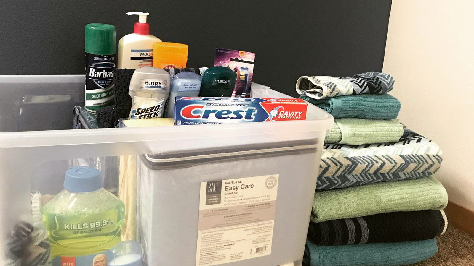 Stack of towels and container with sheets, personal care and cleaning products