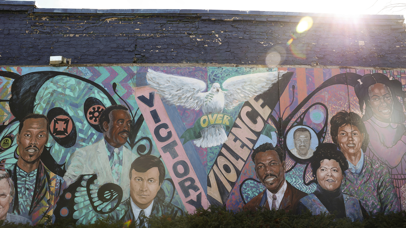 "Mural with potraits and dove with ""Victory Over Violence"" label"