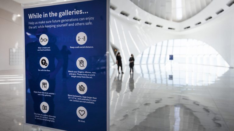 A sign instructs on safety protocols near the entrance to the Milwaukee Art Museum
