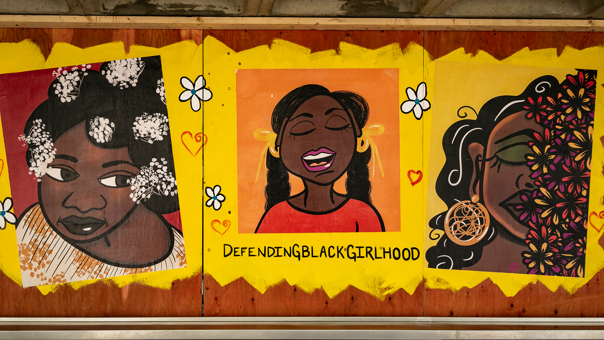 """A vibrant painted mural of three black women across three storefront panels with the words """"Defending Black Girlhood"""""""