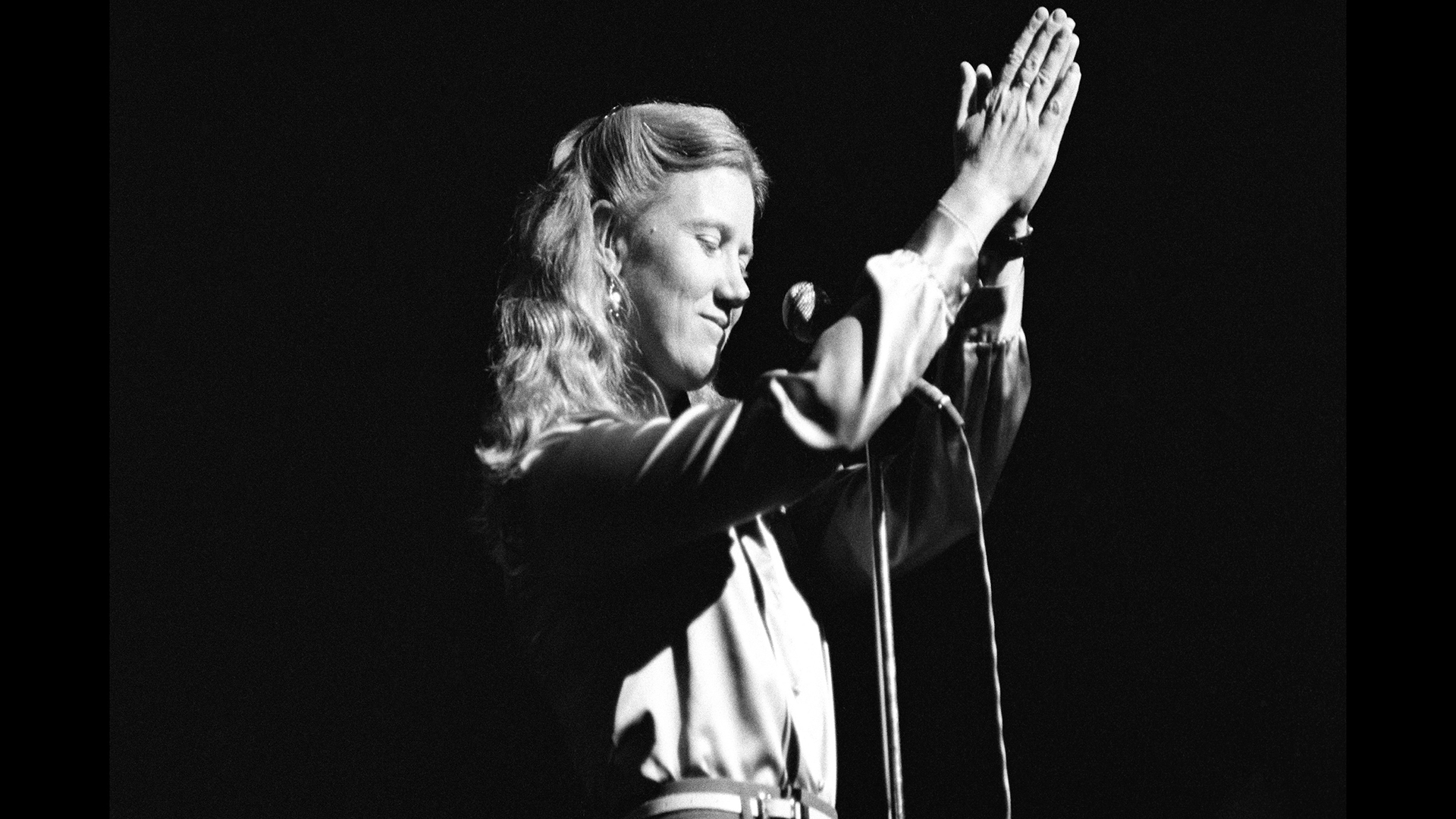 Female singer Holly Near holds her hands in prayer position over her head while standing in front of a microphone.