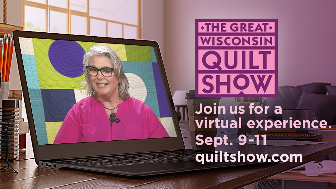 A laptop sits on a desk open to a woman on the screen presenting next to a quilt