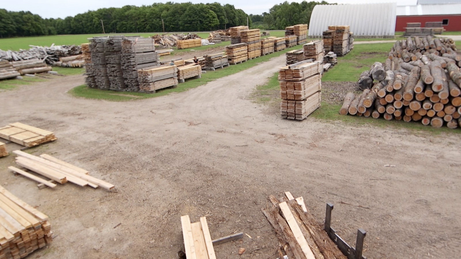 Rows of lumber and timber stacks with storage buildings in background
