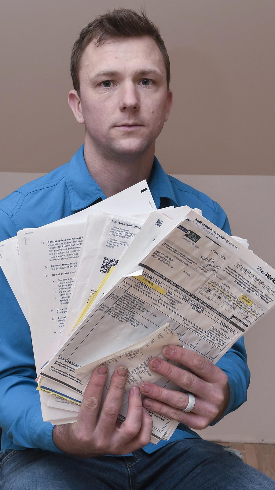 Hands holding multiple medical bills