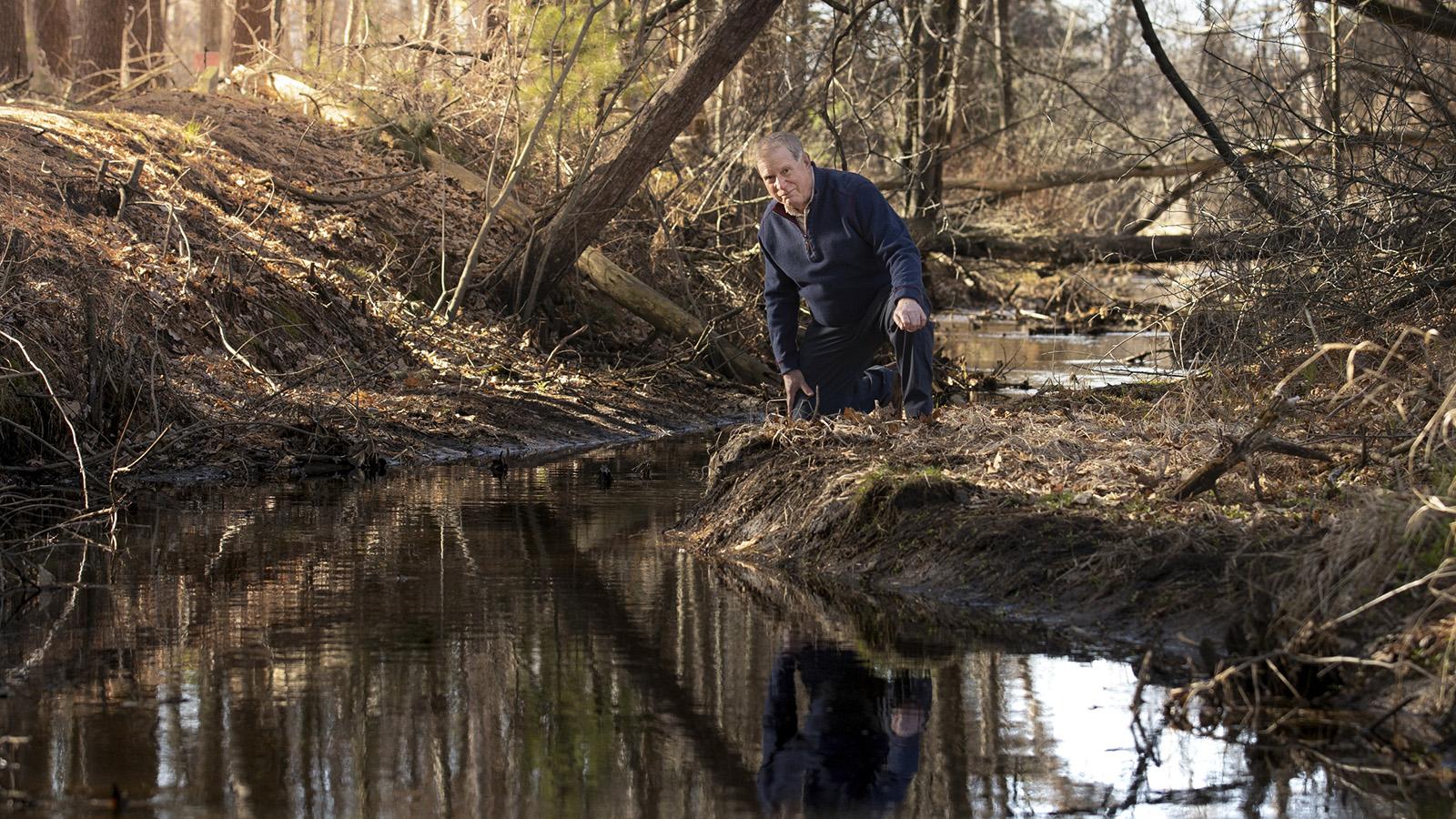 Man kneeling at edge of creek in wooded area