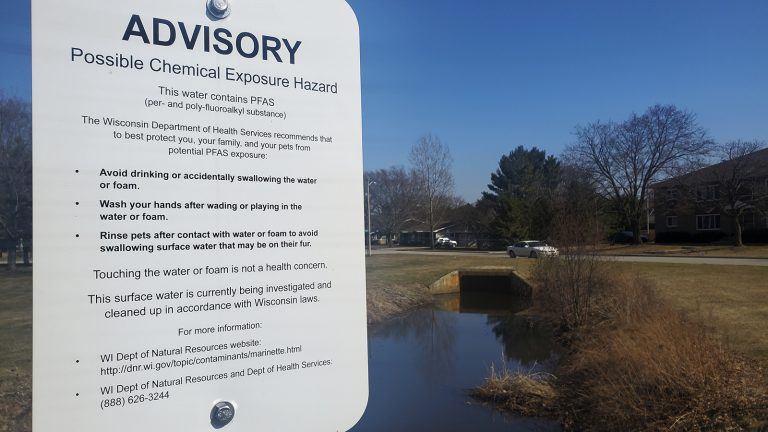 Sign warning of possible chemical exposure hazard above ditch and culvert with houses in background