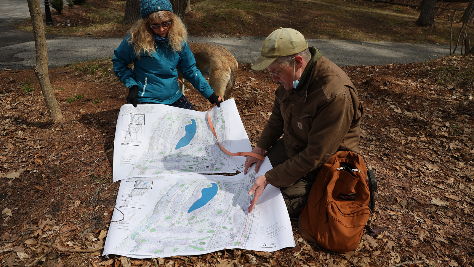 Two people crouch on ground and examine map of proposed golf course