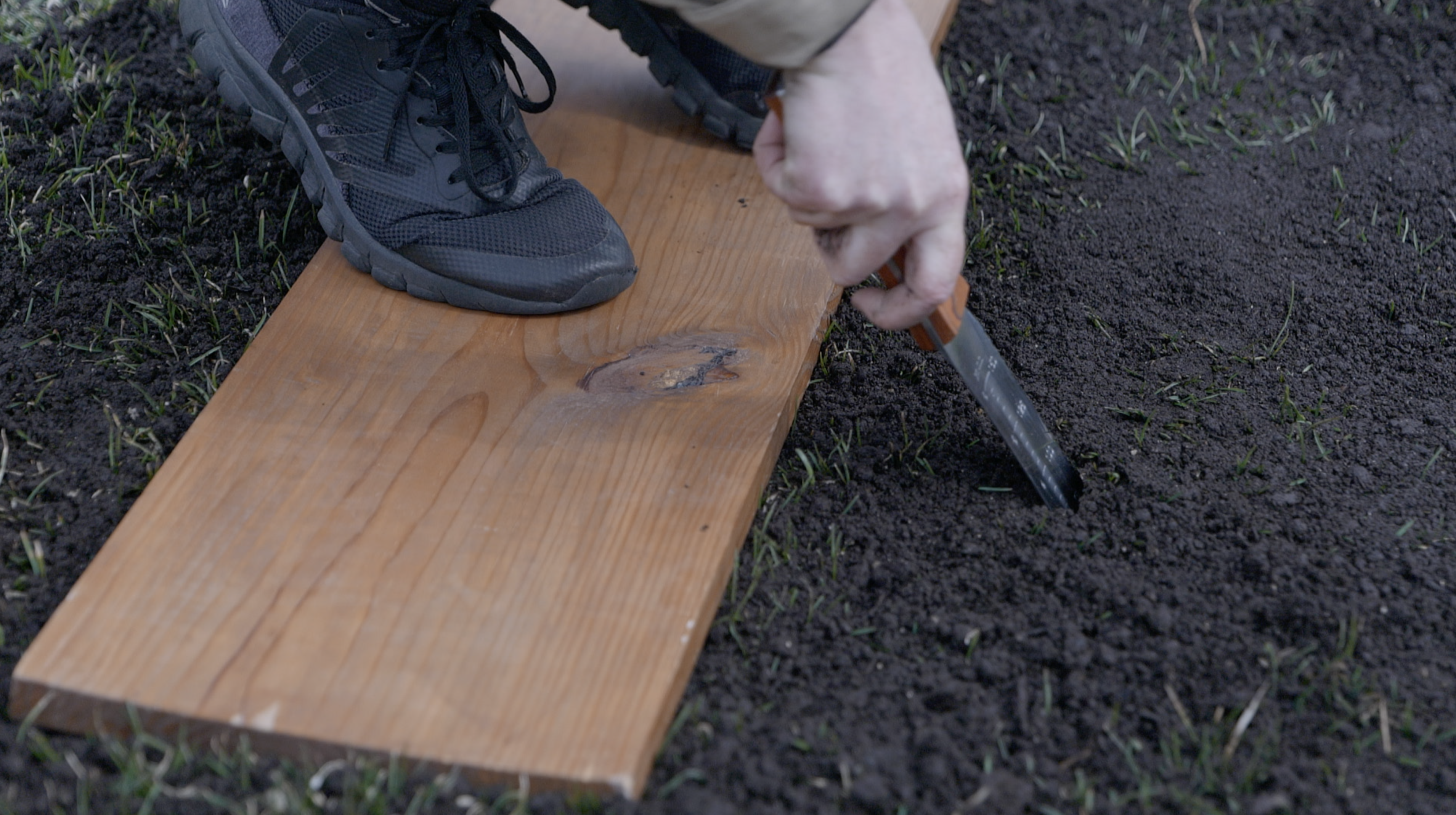 person standing on wooden board in garden bed starting to dig a hole