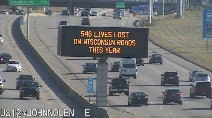 """A digital traffic sign over a highway reads """"546 Lives Lost on Wisconsin Roads This Year."""""""